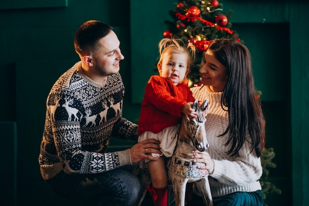 Family with little daughter by christmas tree playing with wooden pony