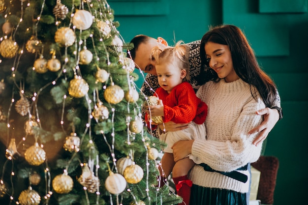 Family with little daughter hanging toys on christmas tree