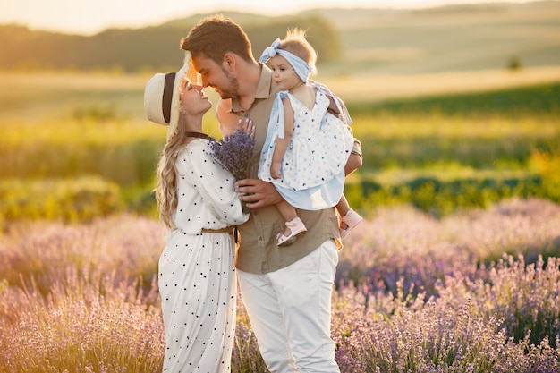 Family with little daughter on lavender field. beautiful woman and cute baby playing in meadow field. family holiday in summer day.