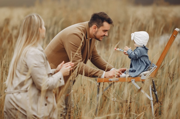 Family with little daughter painting in a autumn field