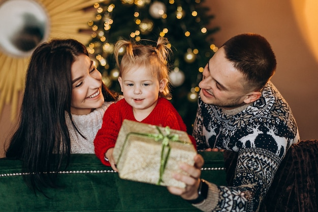 Family with little daughter sitting by christmas tree and unpacking gift box