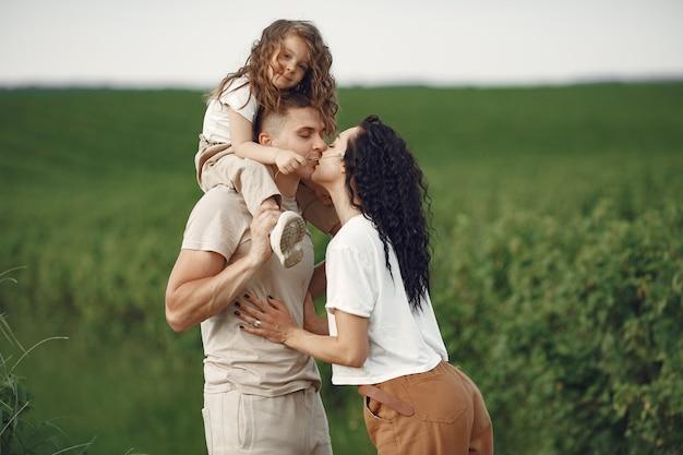日当たりの良いフィールドで一緒に時間を過ごす小さな娘と家族