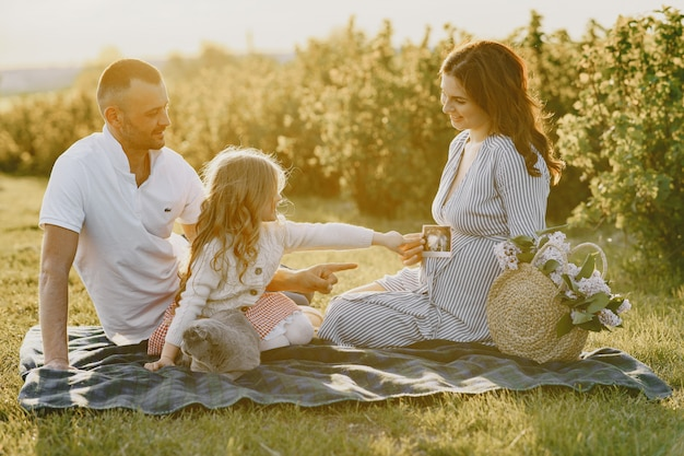 Family with little daughter spending time together in sunny field