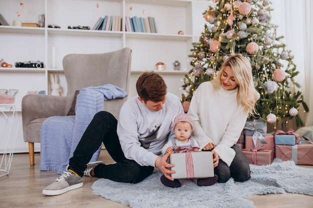 Family with little daughter unpacking gifts by christmas tree