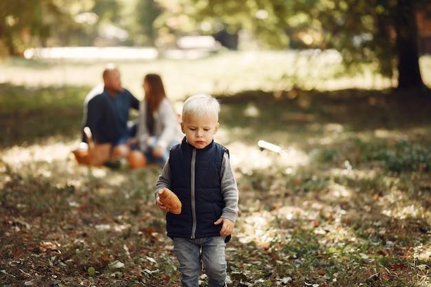 Famiglia con figlio piccolo in un parco in autunno