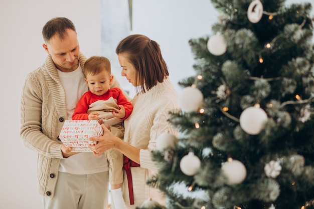 Family with little son on christmas by christmas tree at home