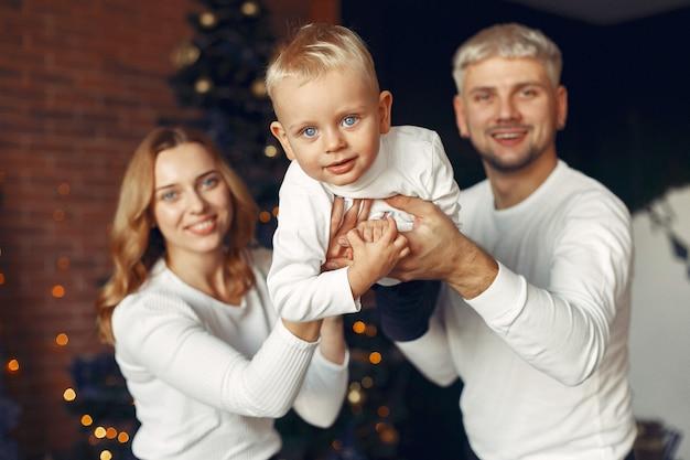 Famiglia con figlio piccolo a casa vicino all'albero di natale