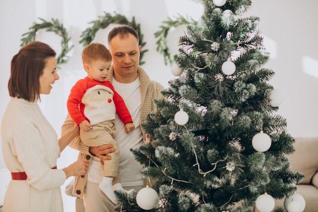 Семья с маленьким сыном на рождество у елки дома