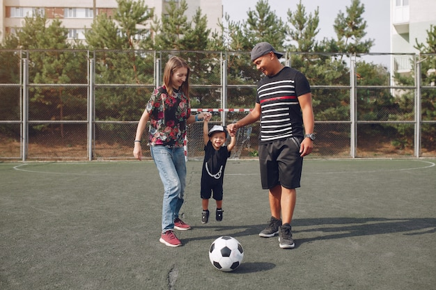 Family with little son playing football