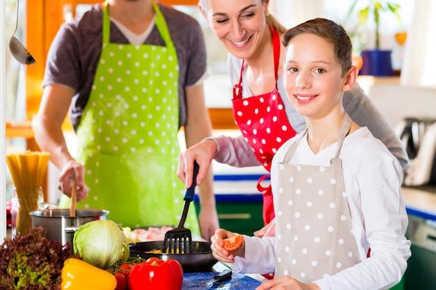 Семья с родителями и детьми готовит здоровую еду на домашней кухне, весело