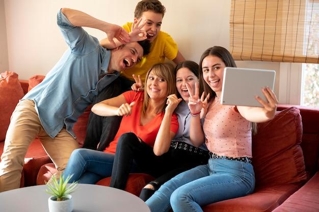 Семья с родителями и вместе делают селфи с планшетом на диване