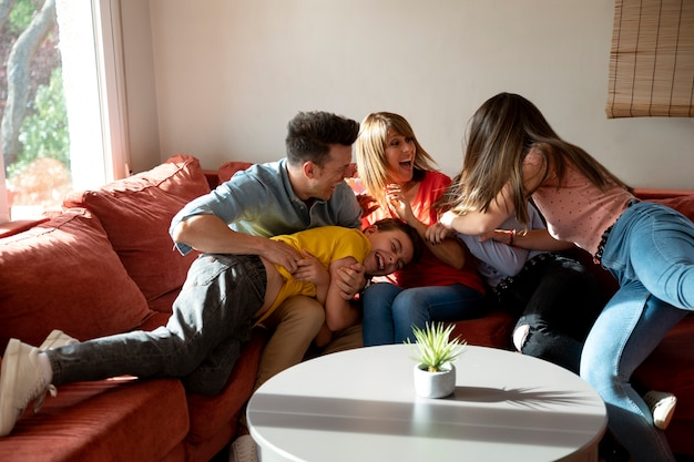 Famiglia con genitori e bambini che si divertono insieme sul divano
