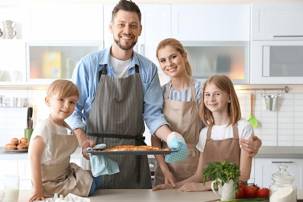 주방에서 피자와 함께 가족입니다. 요리 수업 개념