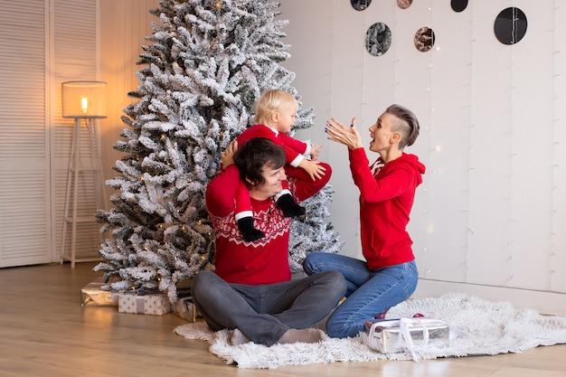 部屋にプレゼントを持っている家族。メリークリスマスとハッピーホリデー。屋内で楽しんでいる両親とその小さな男の子。