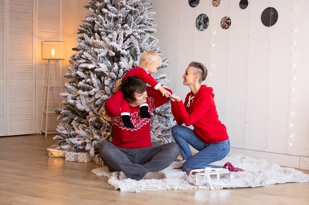 部屋にプレゼントを持っている家族。メリークリスマスとハッピーホリデー。屋内で楽しんでいる親とその小さな子供。