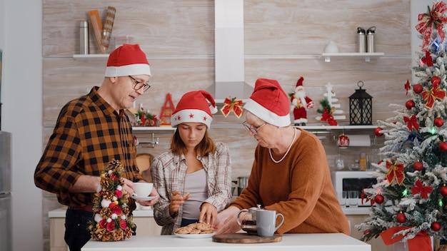一緒にクリスマスを楽しんでクリスマス休暇をスピードアップするサンタ帽子を持つ家族