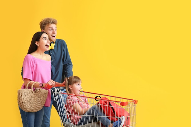 Family with shopping cart on color