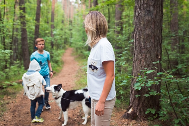Семья с сибирской хаски гуляет в лесу