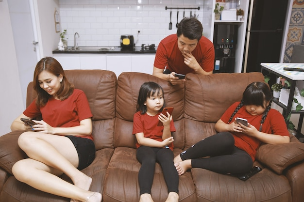 Family with small two daughters sitting on sofa absorbed in devices parents and childs holds smart phone play games use apps overuse of internet digital gadgets bad habit addiction concept