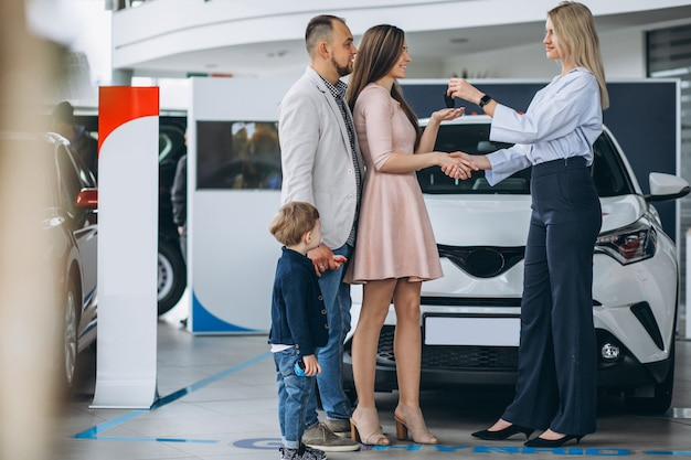 Family with son choosing a car in a car showroom