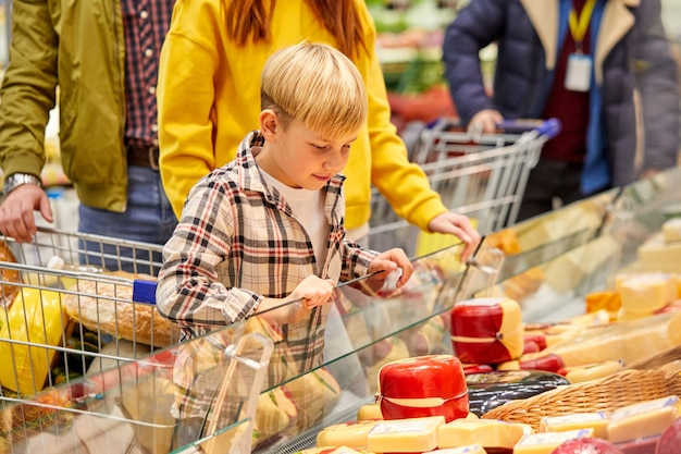 息子が食料品店でチーズを選び、製品のショーケースを見て、話し合っている家族。ショップ、食品、食料品のコンセプト