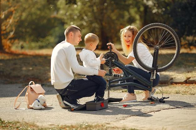 Семья с сыном ремонтируют велосипед в парке