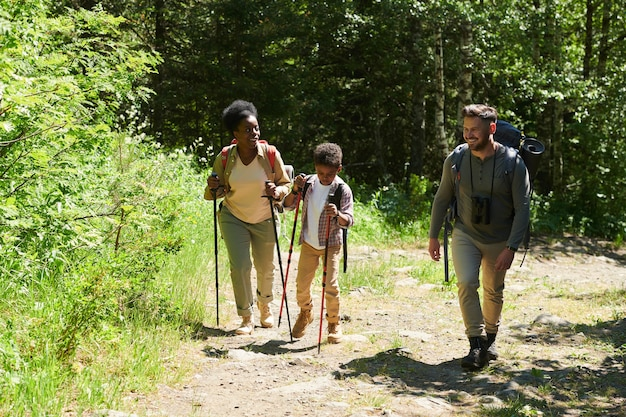 Family with son travelling together through the forest they have backpacks behind the backs and they walking using sticks
