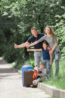 Семья с чемоданами голосует на дороге.