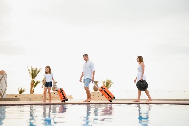 美しいスイミングプールのあるホテルの建物に歩いてスーツケースを持っている家族。旅行のコンセプト。