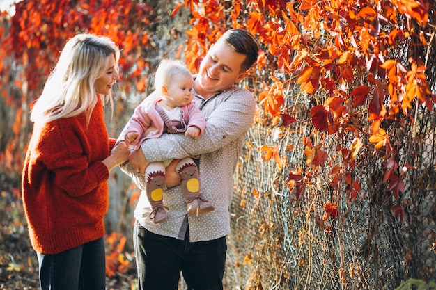 Family with their baby daughter in an autumn park