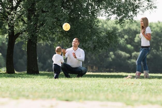 Семья с маленьким сыном на прогулке в городском парке