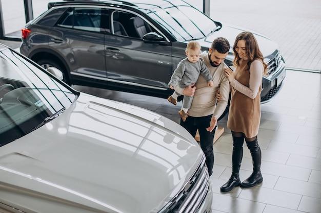 車のショールームで車を選ぶ幼児の女の子を持つ家族