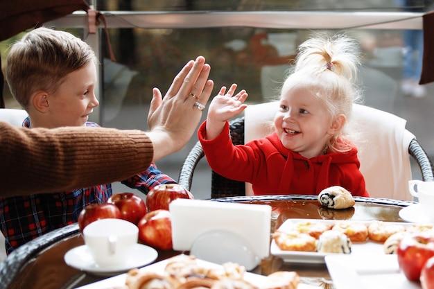Семья с двумя детьми за столиком в кафе. девушка здоровается ладонью.