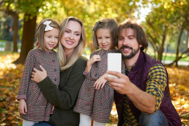 가을 숲에서 셀카를 만드는 두 아이를 둔 가족