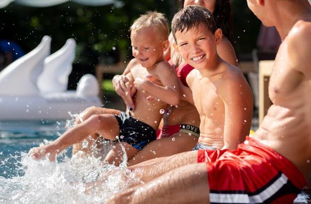 Семья с двумя детьми, наслаждаясь днем в бассейне