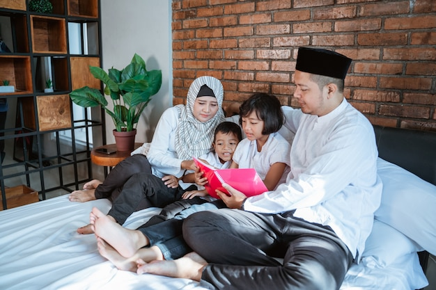 Family with two kids read books together