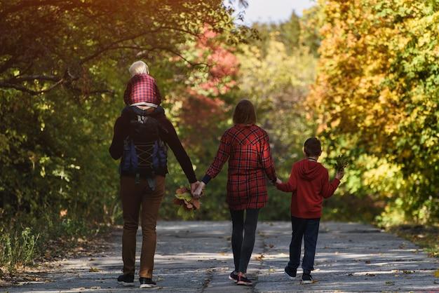 秋の森を歩く2人の息子と家族。