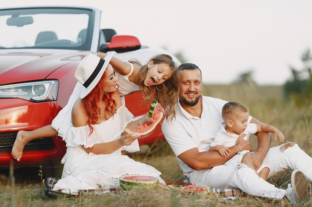 Family with watermelon. father in a white t-shirt. people in a picnic.