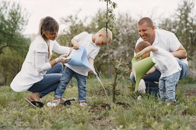 작은 아들이있는 가족은 마당에 나무를 심고 있습니다.
