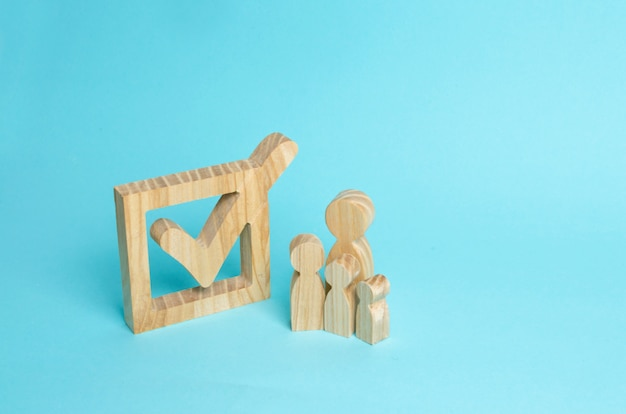 Family wooden human figures stand together next to a tick in the box.