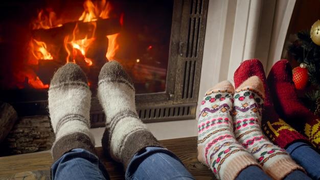 Family in wool socks celebrating christmas at burning fireplace