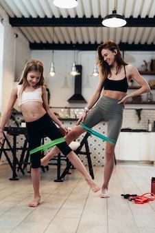 家族はゴムバンドで家で運動しています。