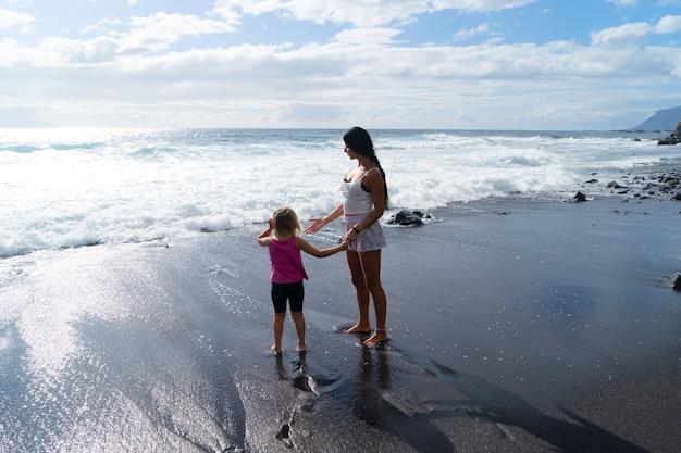 Семейная тренировка. молодая спортивная мать и маленькая дочь в спортивной одежде тренируются вместе на пляже у моря, наслаждаясь природой на берегу. концепция здорового образа жизни