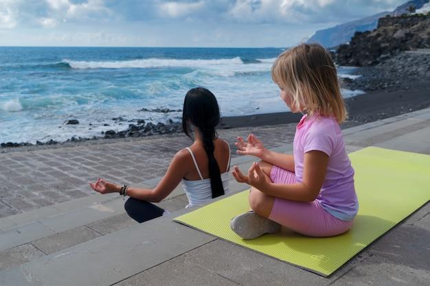 Семейная тренировка. молодая спортивная мать и маленькая дочь в спортивной одежде, тренируясь вместе, растягиваясь на циновке, глядя на море. концепция здорового образа жизни