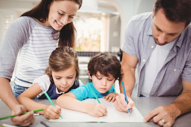 Family writing in book while standing at table
