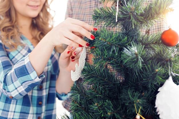 Семья, рождество, зимние каникулы и люди концепции - крупный план счастливой молодой пары, украшающей елку дома