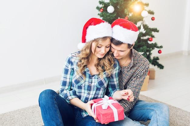 家族、クリスマス、冬休み、人々のコンセプト-自宅のクリスマスツリーの近くで抱き締める幸せなカップル。