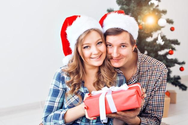 Семья, рождество, зимние каникулы и люди концепции - счастливая пара обниматься возле елки дома.