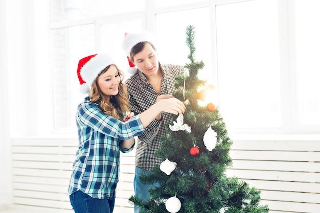 Семья, рождество, зимние праздники и люди концепции - счастливая молодая пара украшает елку дома.