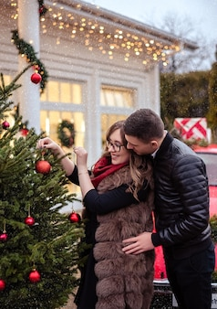 Family, x-mas, winter holidays and people concept - happy couple decorating christmas tree